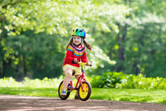 Kids ride balance bike in park Royalty Free Stock Images