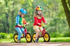 Kids ride balance bike in park royalty free stock image