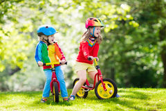 Kids ride balance bike in park Stock Image