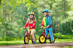Kids ride balance bike in park Royalty Free Stock Photo