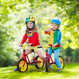 Kids ride balance bike in park. Children riding balance bike. Kids on bicycle in sunny park. Little girl and boy ride glider bike on warm summer day. Preschooler Royalty Free Stock Photo