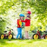 Kids ride balance bike in park Stock Photos