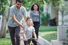 Kids ride bicycle push by his father Stock Photo