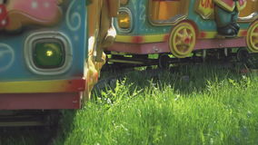 Kids ride on little electric train outdoors. Kids ride on little electric train with the colorful railway cars outdoors in park summer time stock video footage