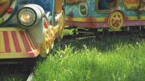 Kids ride on little electric train outdoors. Kids ride on little electric train with the colorful railway cars outdoors in park summer time stock footage