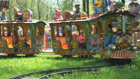 Kids ride on little electric train outdoors. VELIKIY NOVGOROD, RUSSIA - JUNE 15, 2016: Kids ride on little electric train with the colorful railway cars outdoors stock video