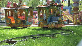 Kids ride on the little electric train in park. Little kids ride on attraction in the form of little electric train with the colorful railway cars outdoors in stock video footage