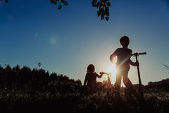 Kids riding bike and scooter at sunset Royalty Free Stock Images
