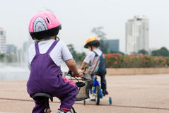 Kids riding bikes. Two young children wearing a helmet riding his bicycle in a park Stock Photography