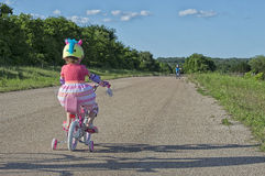 Girl on Bicycle. Little girl with training wheels riding her bicycle Royalty Free Stock Images