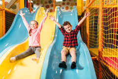Kids riding from childrens slides in game center Royalty Free Stock Photos
