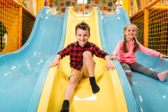 Kids riding from childrens slides in game center Stock Image