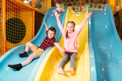 Kids riding from childrens slides in game center Royalty Free Stock Photography