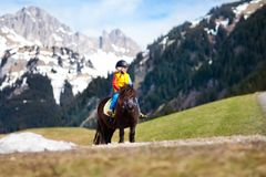 Kids riding pony. Child on horse in Alps mountains. Kids riding pony in the Alps mountains. Family spring vacation on horse ranch in Austria, Tirol. Children Royalty Free Stock Photos