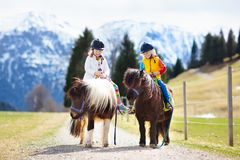 Kids riding pony. Child on horse in Alps mountains. Kids riding pony in the Alps mountains. Family spring vacation on horse ranch in Austria, Tirol. Children stock images