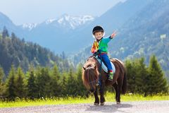 Kids riding pony. Child on horse in Alps mountains. Kids riding pony in the Alps mountains. Family spring vacation on horse ranch in Austria, Tirol. Children royalty free stock photo