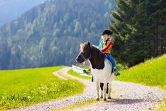 Kids riding pony. Child on horse in Alps mountains Royalty Free Stock Photos