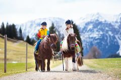 Kids riding pony. Child on horse in Alps mountains. Kids riding pony in the Alps mountains. Family spring vacation on horse ranch in Austria, Tirol. Children Stock Photography