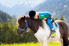 Kids riding pony. Child on horse in Alps mountains Stock Images