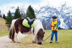 Kids riding pony. Child on horse in Alps mountains. Kids riding pony in the Alps mountains. Family spring vacation on horse ranch in Austria, Tirol. Children Stock Photo