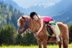 Kids riding pony. Child on horse in Alps mountains Royalty Free Stock Photography