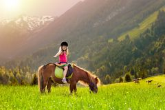 Kids riding pony. Child on horse in Alps mountains Stock Photos