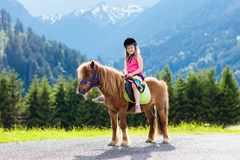Kids riding pony. Child on horse in Alps mountains Royalty Free Stock Photo