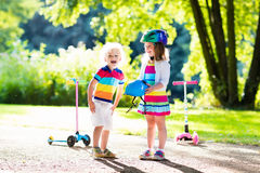 Kids riding scooter in summer park. Children learn to ride scooter in a park on summer day. Preschooler girl helping boy to put on safety helmet. Siblings royalty free stock photography