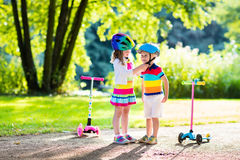 Kids riding scooter in summer park. Children learn to ride scooter in a park on summer day. Preschooler girl helping boy to put on safety helmet. Siblings stock photos