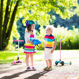 Kids riding scooter in summer park. Children learn to ride scooter in a park on summer day. Preschooler girl helping boy to put on safety helmet. Siblings stock photography