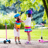 Kids riding scooter in summer park. Children learn to ride scooter in a park on summer day. Preschooler girl helping boy to put on safety helmet. Siblings stock images