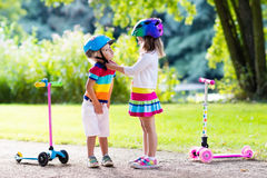 Kids riding scooter in summer park. Children learn to ride scooter in a park on summer day. Preschooler girl helping boy to put on safety helmet. Siblings royalty free stock images