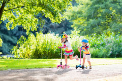 Kids riding scooter in summer park. stock photos