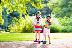 Kids riding scooter in summer park. Children learn to ride scooter in a park on sunny summer day. Preschooler boy and girl in safety helmet riding a roller royalty free stock image