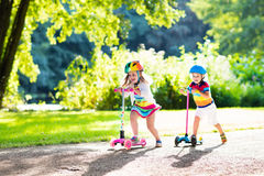 Kids riding scooter in summer park. stock images