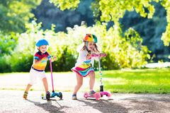 Kids riding scooter in summer park. Children learn to ride scooter in a park on sunny summer day. Preschooler boy and girl in safety helmet riding a roller stock photos