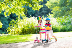 Kids riding scooter in summer park. Children learn to ride scooter in a park on sunny summer day. Preschooler boy and girl in safety helmet riding a roller stock image