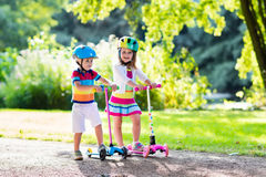 Kids riding scooter in summer park. Children learn to ride scooter in a park on sunny summer day. Preschooler boy and girl in safety helmet riding a roller Stock Photography