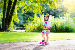 Kids riding scooter in summer park. Little child learning to ride a scooter in a city park on sunny summer day. Cute preschooler girl in safety helmet riding a royalty free stock images