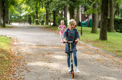 Kids riding scooter Stock Images