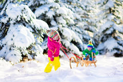 Kids riding a sleigh in snowy winter park Stock Images