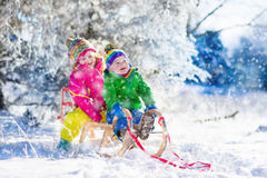 Kids riding a sleigh in snowy winter park Royalty Free Stock Photos