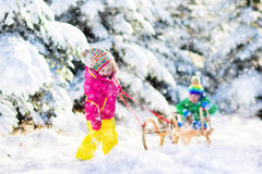 Kids riding a sleigh in snowy winter park. Little girl and boy enjoying sleigh ride.  sledding. Toddler kid riding a sledge. Children play outdoors in snow. Kids Royalty Free Stock Photography