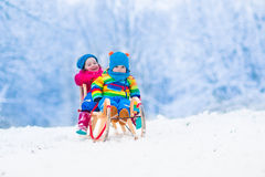 Kids riding sleigh in winter park. Little girl and baby boy enjoying a sleigh ride. Child sledding. Toddler kid riding a sledge. Children play outdoors in snow Royalty Free Stock Images
