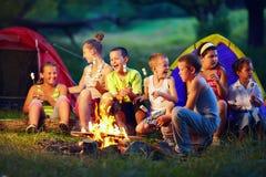 Kids roasting marshmallows on campfire stock photo