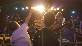 Kids at rock concert. Kids in front of stage at rock concert in Hard Rock Cafe stock image