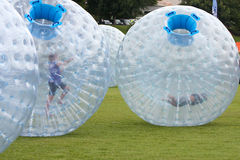 Kids Roll Around In Large Zorbs At Summer Festival Stock Photography