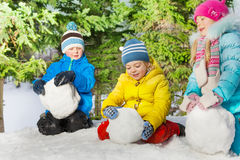 Kids roll snow balls in the park Stock Images