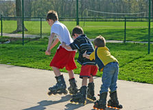 Kids Roller-Blading. In a Row Holding on to each other Royalty Free Stock Photo