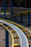 Kids roller coaster yellow rails in amusement park. Kids roller coaster yellow rails in amusement park in the afternoon stock photos
